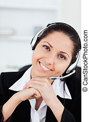 Smiling operator with headset in her office