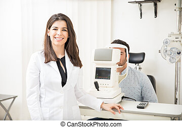 Smiling optometrist examining young patient on tonometer in ophthalmology clinic