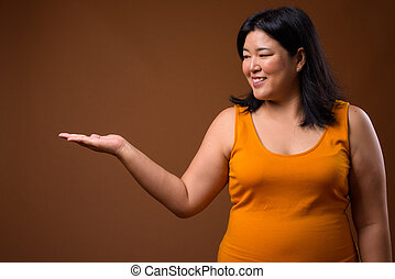 Smiling overweight Asian woman showing copy space