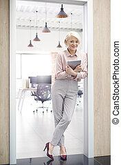 Smiling owner of office standing in doorway