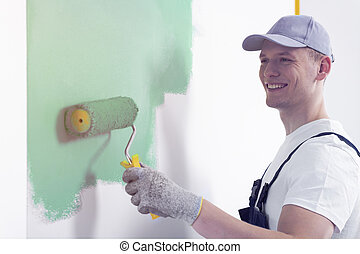 Smiling painter with roller painting wall on green while redecorating interior