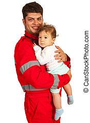 Smiling paramedic man holding baby