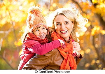 Smiling parent and kid family walking together outdoor in yellow