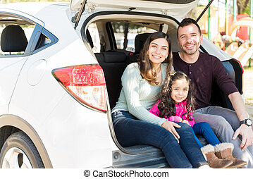 Smiling Parents And Daughter In Car