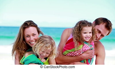 Smiling parents holding their children on the beach
