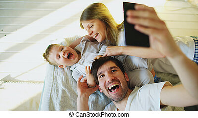 Smiling parents with baby taking selfie family photo on bed at home