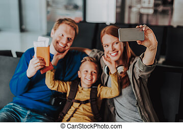 Smiling parents with boy are taking selfie at airport -...