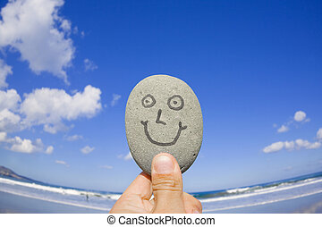 Wide angle shot of a smailing pebble in front of a sandy beach.