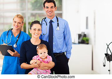 medical professionals with mother and baby girl