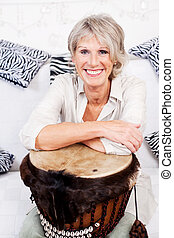 Smiling pensioner with a drum