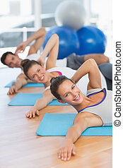 Smiling people doing pilate exercises in fitness studio -...