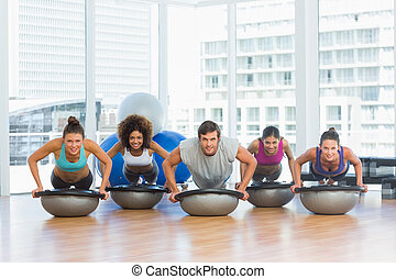 Smiling people doing push ups in fitness studio
