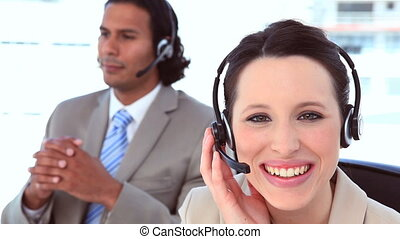 Smiling people in suit using headsets