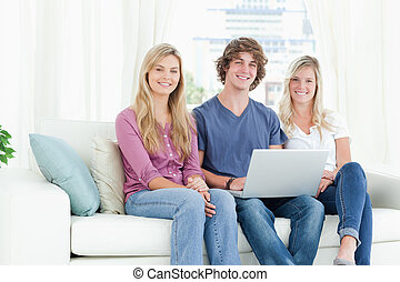Smiling people on the couch as they use the laptop