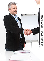 smiling people shaking hands in office. businessman shaking hands to seal deal with his partner and smiling