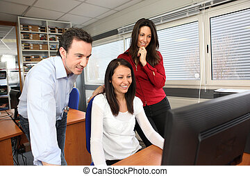 Smiling people using a computer in an office