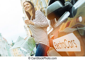 Smiling person standing with a map and a cup of coffee