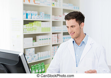 Smiling pharmacist checking stock on his computer - Smiling...