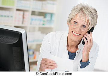 Smiling pharmacist checking up on a prescription