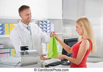 Smiling Pharmacist Giving Medicines To Customer