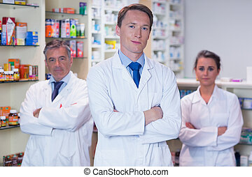 Smiling pharmacy team standing with arms folded