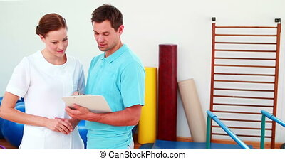 Smiling physical therapists looking at clipboard at the...