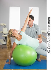 Smiling physiotherapist correcting patient doing exercise on exercise ball in bright room