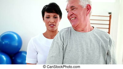 Smiling physiotherapist helping elderly patient lift hand...