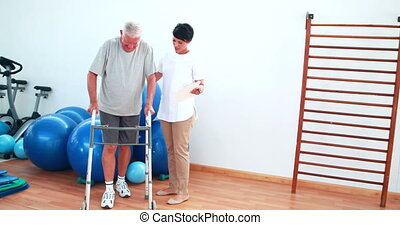 Smiling physiotherapist helping patient walk with walking...