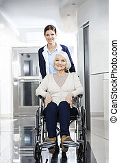 Smiling Physiotherapist Pushing Senior Woman In Wheelchair
