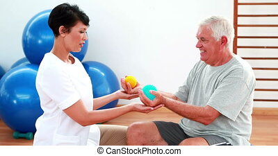 Smiling physiotherapist squeezing massage balls with patient...
