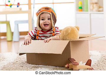 Smiling pilot aviator baby boy with teddy bear toy plays in cardboard box