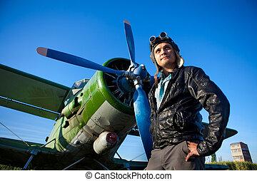 Smiling pilot in the helmet in front of vintage plane