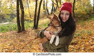 Smiling playful girl with dog on autumn day