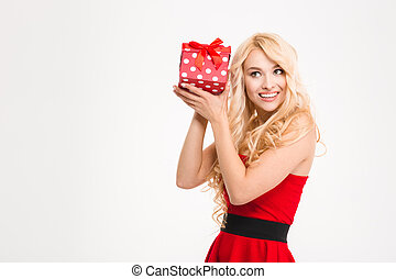 Smiling playful young woman in red dress posing with gift