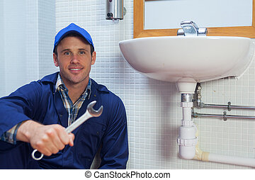 Smiling plumber holding wrench sitting next to sink in...