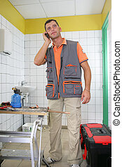 Smiling plumber on the phone