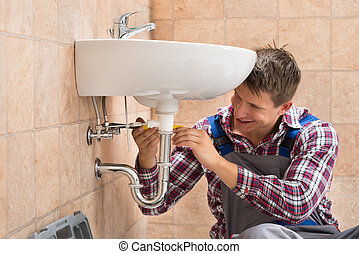 Smiling Plumber Repairing Sink