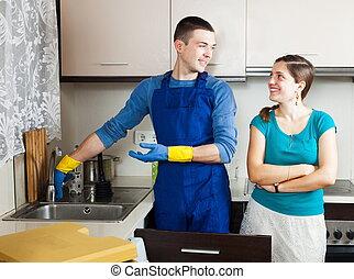 Smiling plumber repairing  water lines