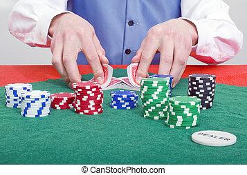 A dealer shuffling cards at a poker table
