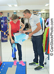 smiling positive couple examining various sports clothes in sports store