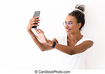 Smiling positive young african woman with dreads posing isolated over white wall background take selfie by mobile phone.
