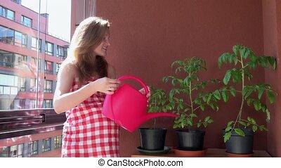smiling pregnant female girl watering plants in balcony on sunlight