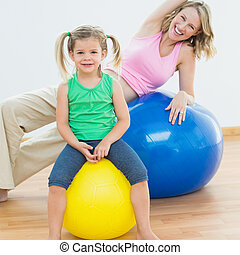 Smiling pregnant woman exercising on exercise ball with...