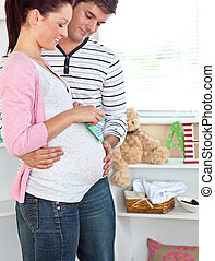 Smiling pregnant woman holding baby shoes while husband...