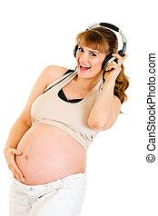 Smiling pregnant woman holding her belly and listening music in headphones  isolated on white