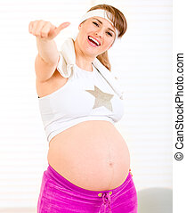Smiling pregnant woman in sportswear showing thumbs up ...