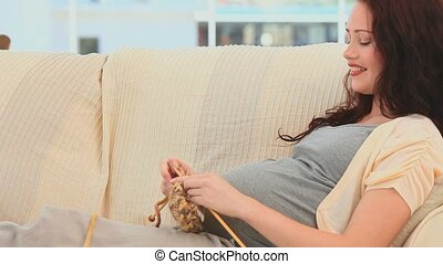 Smiling pregnant woman knitting