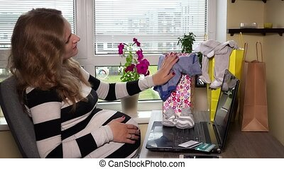 Smiling pregnant woman looking at baby clothes after...