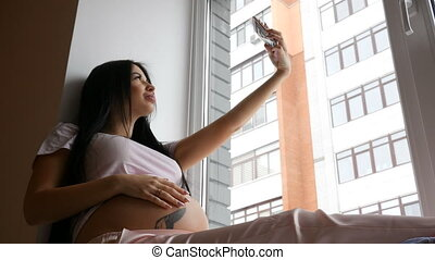 Smiling Pregnant Woman posing on window sill and do selfie